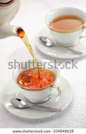 Pouring tea from the tea pot into the cups on, white background