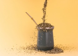 Pouring traditional Yerba Mate tea saturating in a cup of mate with a metal straw bulb accompanied by an author's book, photographed with a soft background.