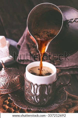 Pouring turkish coffee into traditional embossed metal cup.Toned
