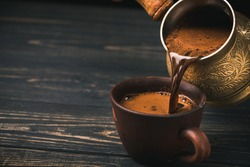 Pouring turkish coffee into vintage cup on wooden background