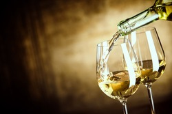Pouring two glasses of white wine from a bottle in a close up view of the wineglasses over an abstract brown blue background with copy space