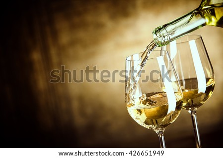 Pouring two glasses of white wine from a bottle in a close up view of the wineglasses over an abstract brown blue background with copy space #426651949