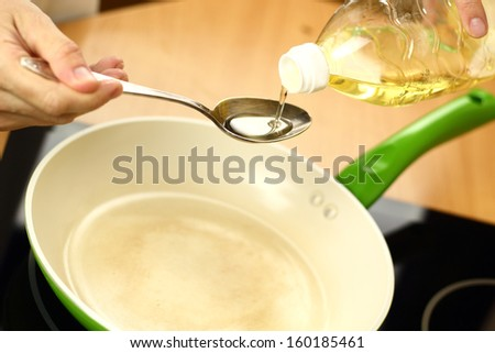 Pouring vegetable oil into frying pan. Making enchilada tortilla with beef.