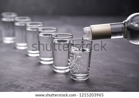 Pouring vodka into the glass on a black background, selective focus Zdjęcia stock ©