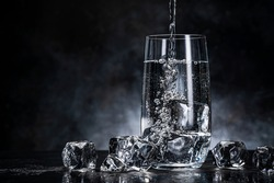 Pouring water from bottle into glass with ice cubes on black background