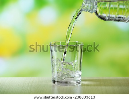 Pouring water from bottle on  glass on bright background