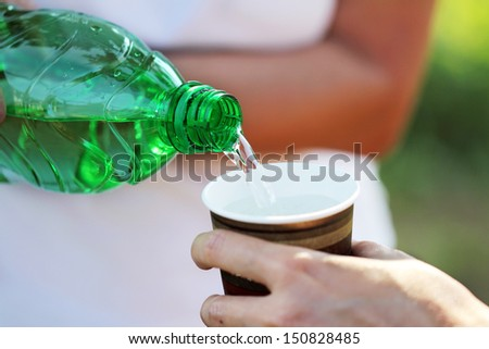 pouring water from green bottle - stock photo