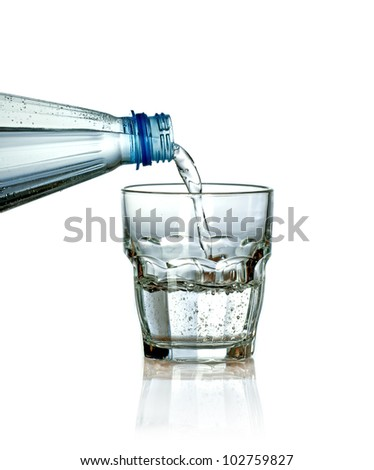 Pouring water from plastic bottle to glass isolated on white background