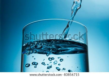 pouring water in glass top closeup in blue light