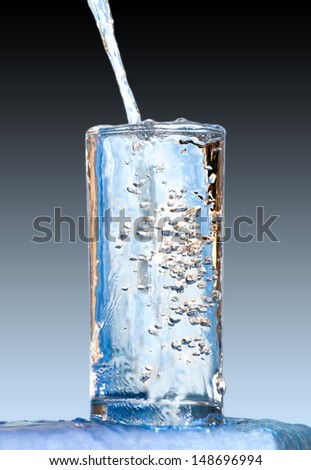 Pouring water into a glass against the  background