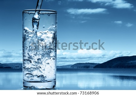 Pouring water into a glass against the nature background