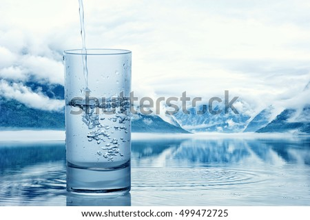 Pouring water into a glass against the nature landscape