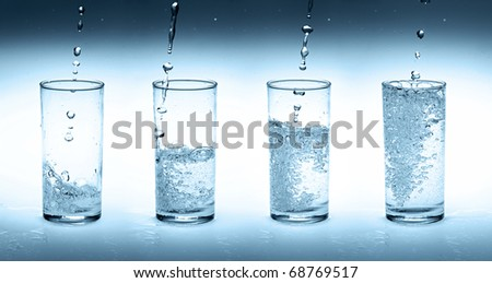 Pouring water into four glasses