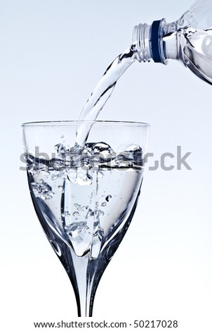 pouring water into glass, grey background - stock photo