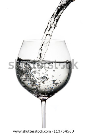 Pouring water into glass isolated
