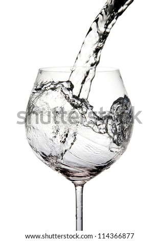 Pouring water into glass isolated on white (splash of water)
