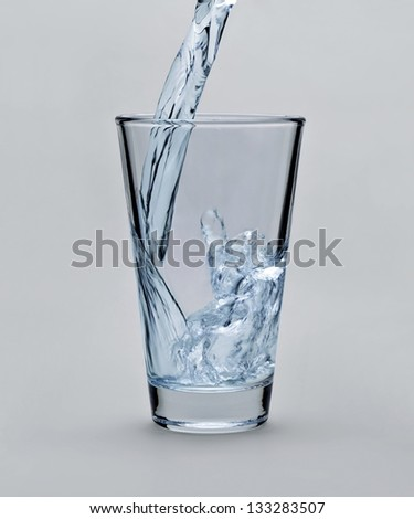 Pouring water into glass on light gray background