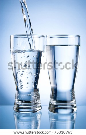 Pouring water into glasson and Glass of water on a blue background