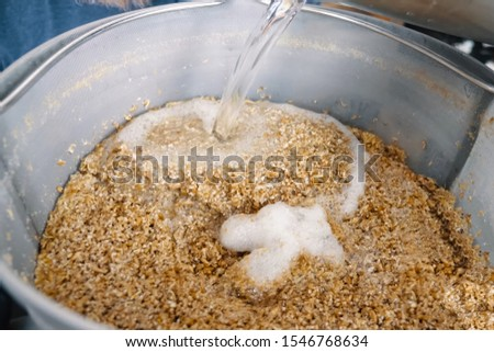 Pouring water into ground barley. Ground barley in a container, grinding barley. #1546768634