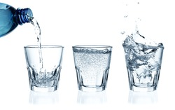 Pouring water on a glass on white background. Ice cubes splashing into glass of water