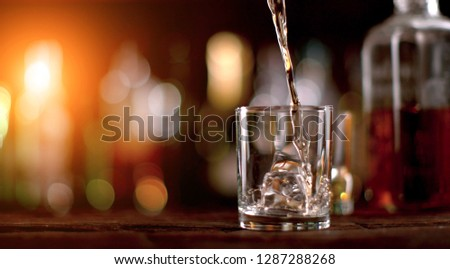 Pouring whiskey into glass. Placed on wooden table. Low depth of focus #1287288268