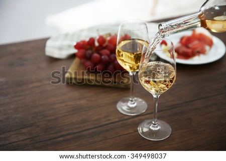 Pouring white wine from bottle into the wineglass on the table