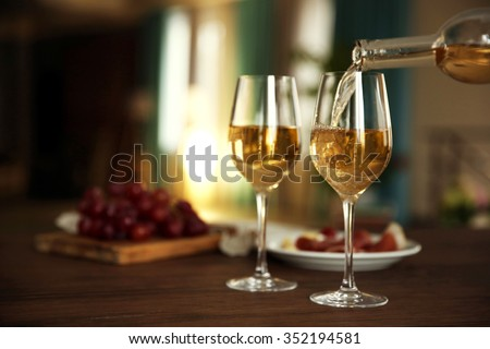 Pouring white wine from bottle into the wineglass on the table over blurred background #352194581