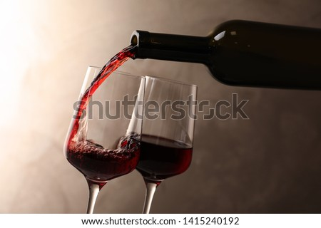 Pouring wine from bottle into glass on color background #1415240192