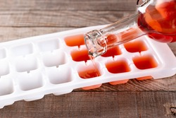 Pouring wine in ice cube tray on a wooden table