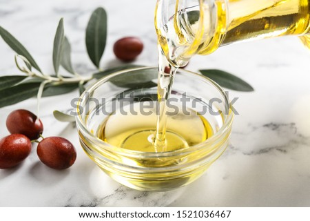 Pouring with jojoba oil from jug into bowl on white marble table