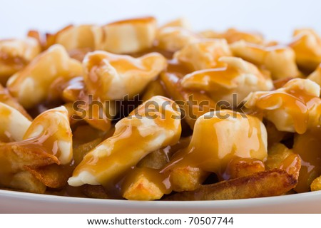 Poutine meal made with french fries, cheese curds and gravy. Macro photography with shallow depth of field.