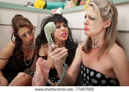 Pouting woman on phone with friends in kitchen
