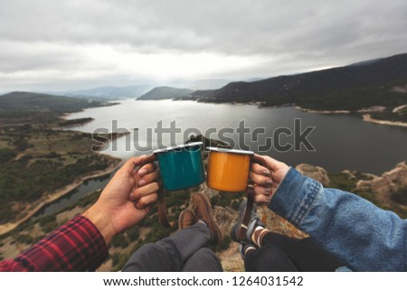 Pov image of couple holding enamel cups on mountain peak