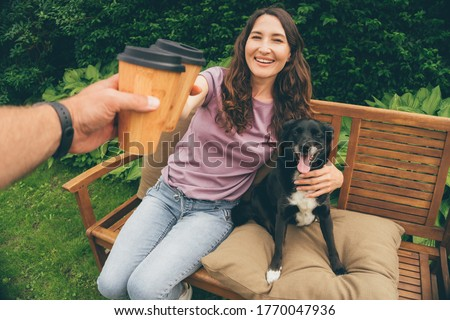 Photo of POV image of young couple toasting with bamboo coffee cups sitting in summer garden with dog - concept of happy family, sustainable living, plastic reduction and ecology