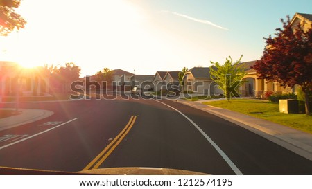 POV, LENS FLARE: Warm evening sun rays shine on the luxury real estates in California. Scenic road trip through the modern suburban neighborhood at sunset. Beautiful luxury houses at autumn sunrise.