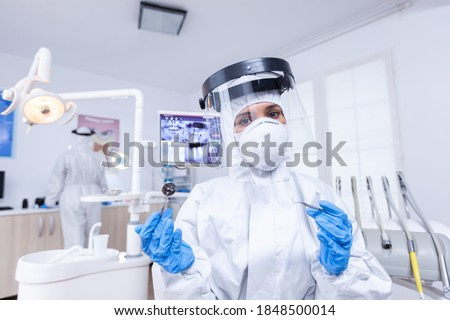 Pov of dentist and assistant in working on patient mouth hygine in suit agasint covid. Stomatolog wearing safety gear against coronavirus during heatlhcare check of patient. Photo stock ©