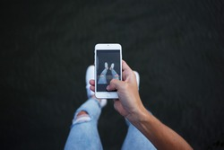 POV of man in trendy fashionable hipster skinny denim jeans making photos of his legs and feet in white sneakers on smartphone for social media