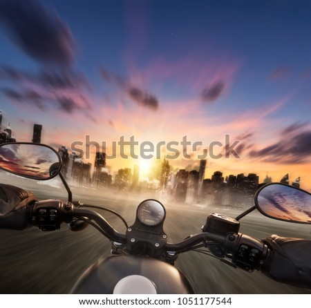 POV of motorcycle driver holding handlebar, heading to modern city skyline. Travel, speed, freedom and transportation topic. Very high resolution image #1051177544