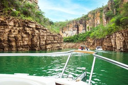 POV of tourist boats navigating between canyons of sedimentary rocks and the green water of the lake. Canyons of Furnas at Capitólio, MG, Brazil.