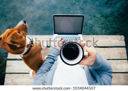 POV of urban millennial or hipster remote worker in startup work on laptop on sea, ocean or park lake wooden pier. Dog and best friend pet by side. Metal jug or cup with fresh coffee to stay awake