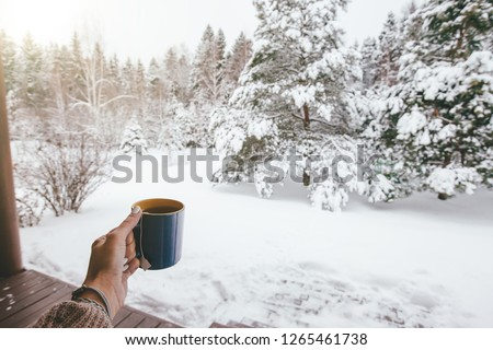 POV photo of mug with hot tea in human hand over snowy forest some winter morning