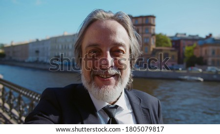 POV shot of mature businessman making video call standing outdoors in city. Successful aged entrepreneur blogger filming video for internet blog or taking selfie over river background