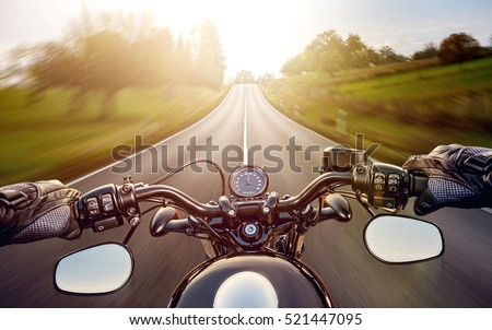 Shutterstock POV shot of young man riding on a motorcycle. Hands of motorcyclist on a street