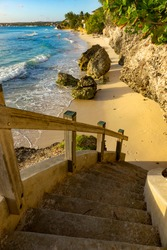 POV VERTICAL: Stairwell leads down to an empty tropical sandy beach in sunny Barbados. Access to a private beach on a picturesque tropical island in the Caribbean. Stairs leading to a golden-lit shore