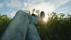 POV view of a farmer's feet in rubber boots in a field. A man is resting lying in the middle of an agricultural field, shaking his leg, against the backdrop of sunlight and blue cloudy sky