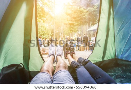 Shutterstock Pov view of happy couple inside tent at camping wood festival - Young people having fun on summer vacation into the wood - Travel,love,nature concept - Main focus on left feet - Warm contrast filter