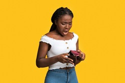 Poverty and absence of money. Shocked african american woman checking empty wallet, frustrated black lady searching for cash, standing isolated over yellow studio background, copy space