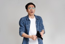 Poverty and absence of money. Unemployed sad asian guy showing empty wallet, looking at camera, standing over light studio background with free space
