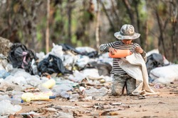 Poverty in India, a child collects garbage in a landfill site, Concept of livelihood of poor children.Child labor. Child labor,  human trafficking, Poverty concept.