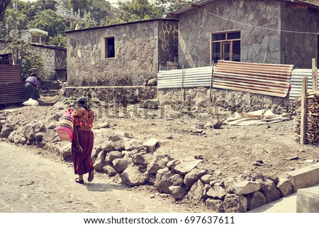 Poverty in Latin America / Poor Woman walking on dusty road in Mexico / Colorful latin clothing